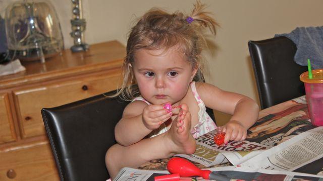 niña pintando uñas