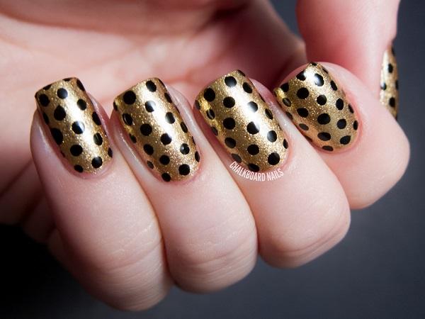 uñas doradas con puntos negros