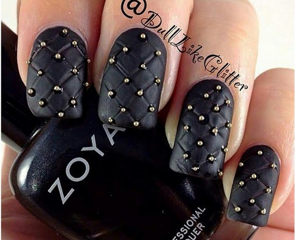 uñas negras con accesorios dorados