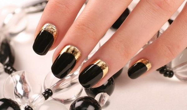 uñas negras con bordes dorados