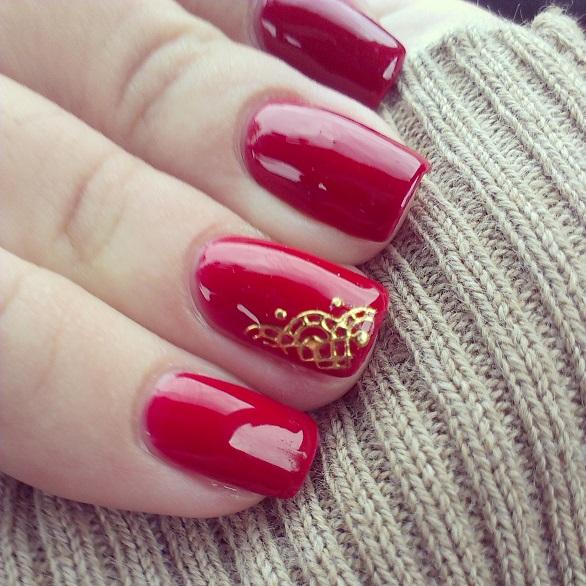 uñas pintadas de rojo y dorado