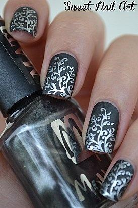 diseño de uñas negro con flores plateadas