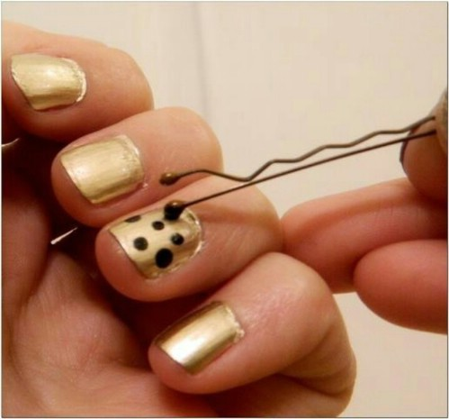puntos en uñas doradas